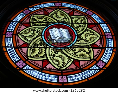 Backlit stained glass window with an open Bible in the center. Circa 1880. - stock photo