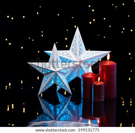 Backlit stars in blue with red candles in front of dark background - stock photo