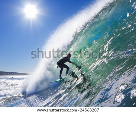 Backlit Surfer on Big Wave in the Tube on a Sunny Blue Sky Day - stock photo