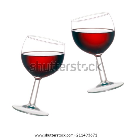 Backlit two glasses of red wine, isolated on white background. Jaunty angle. - stock photo