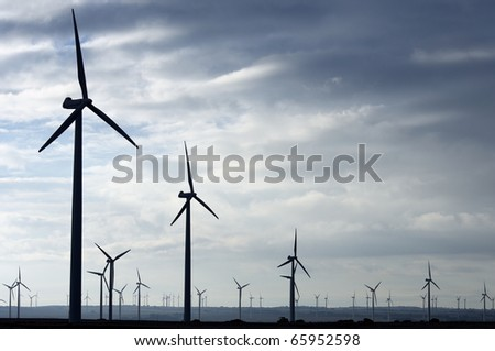 Backlit view of a group of mills for electric power generation - stock photo