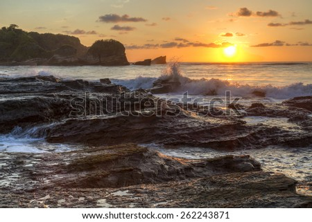 Backlit waves crash onto the rocky shore of Playa Pelada at sunset on the Pacific coast of Costa Rica. - stock photo