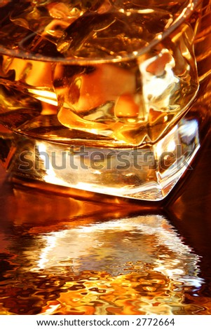 Backlit whiskey in glass tumbler with reflection