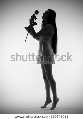 Backlite portrait of young girl with rose on grey (monochrome version) - stock photo