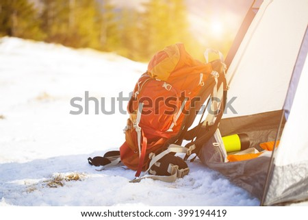 Backpack and belongings for the journey stand near tents in the winter.  - stock photo
