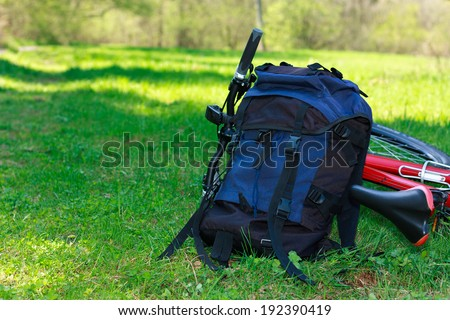 Backpack and Bike lying on green grass against the background of nature in summer on a sunny day - stock photo