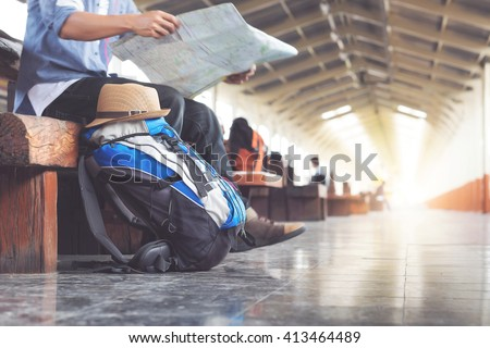 Backpack and hat at the train station with a traveler. Travel concept. - stock photo