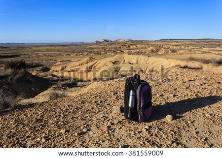 backpack and thermos in mountains - stock photo