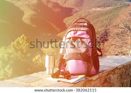 backpack, binoculars, map in mountains, travel - stock photo