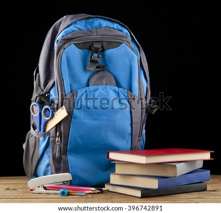 backpack, books and stationery for school isolated on a black background - stock photo