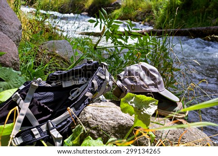 Backpack, sneakers and a cap on the shore of a mountain river