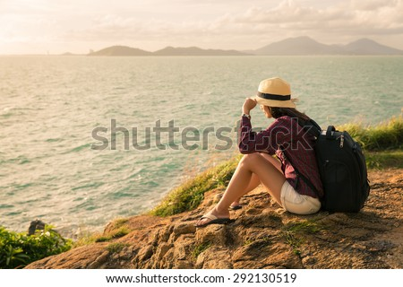 Backpack traveler asia woman sitting on sea cliff in sunset, Koh Samet, Rayong, Thailand - stock photo