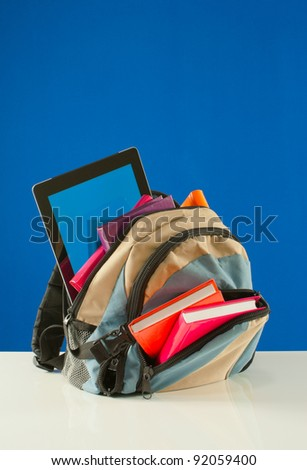 Backpack with colorful books and tablet PC on blue background - stock photo