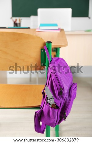 Backpack with knife in classroom, close up. Juvenile delinquency - stock photo