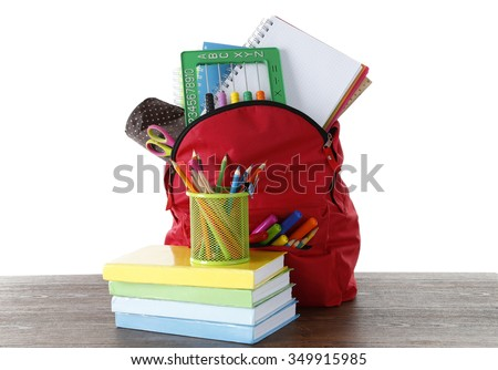 Backpack with school supplies on wooden table   with white background - stock photo