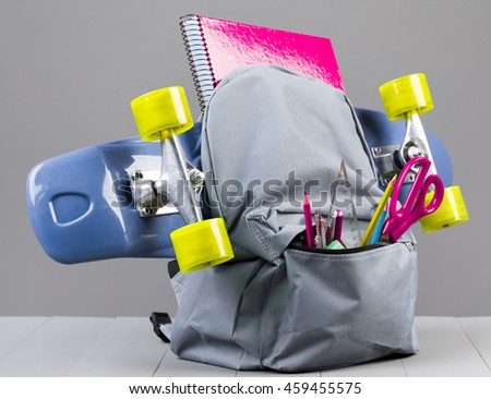 Backpack with skateboard on grey background