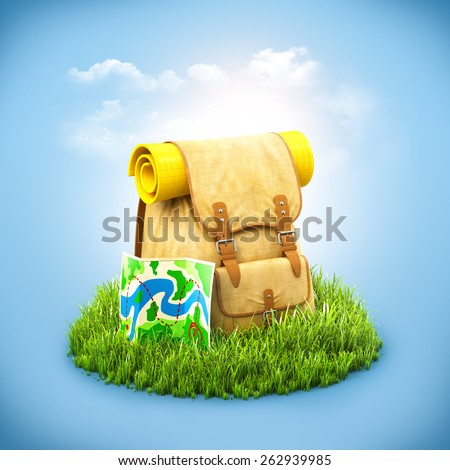 Backpack with the map on grass at blue background. Unusual travel background - stock photo