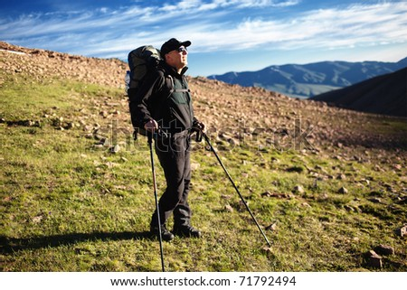 Backpacker admiring the sunrise in the mountains - stock photo