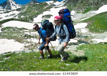 Backpacker couple hiking in mountains with green grass and white snow. - stock photo