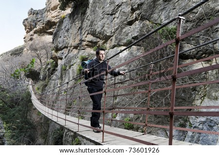 Backpacker crossing a suspension bridge mountain background - stock photo