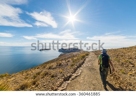 Backpacker exploring the Inca Trails on Island of the Sun, Titicaca Lake, among the most scenic travel destination in Bolivia. Travel adventures and vacations in the Americas. Shot in backlight. - stock photo