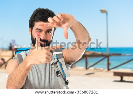 backpacker focusing with his fingers on a white background