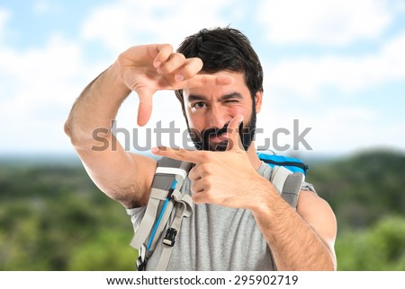 backpacker focusing with his fingers on unfocused background
