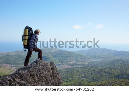 Backpacker girl standing on a high rock over sea - stock photo