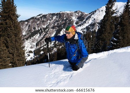 Backpacker goes deep in snow in the mountains - stock photo