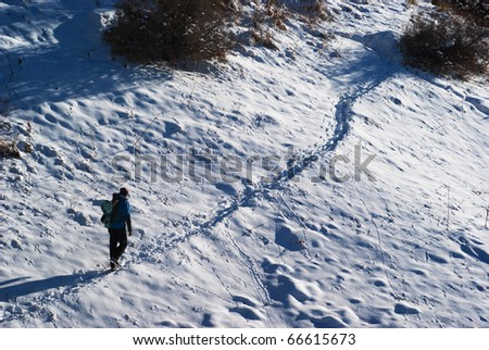 Backpacker goes on winter trail in the mountains - stock photo
