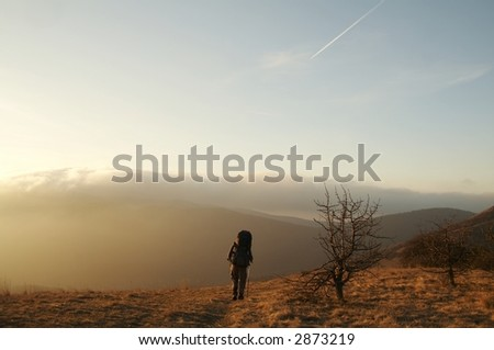 Backpacker going up along hill - stock photo