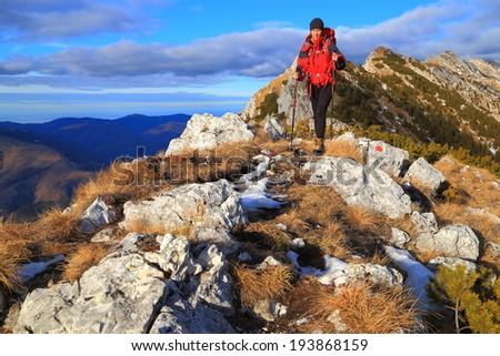 Backpacker hiking across mountain ridge - stock photo