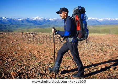Backpacker in wilderness mountains - stock photo