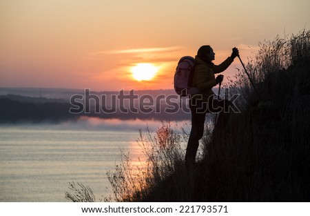 Backpacker is climbing the steep slope. Sunrise and river on the background - stock photo