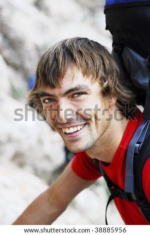 Backpacker Looking at Camera - stock photo