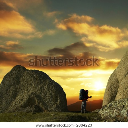 Backpacker looking on sunset - stock photo