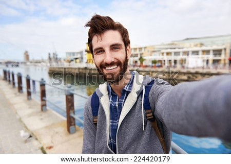 Backpacker man taking selfie on holiday having fun and smiling - stock photo