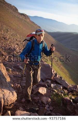 Backpacker on footpath in morning mountains - stock photo