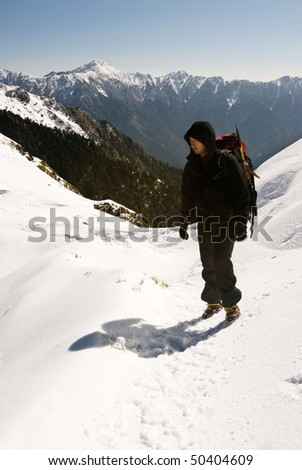 Backpacker on snow mountain path in winter.
