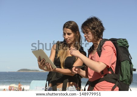 Backpacker on the beach using tablet as map - stock photo
