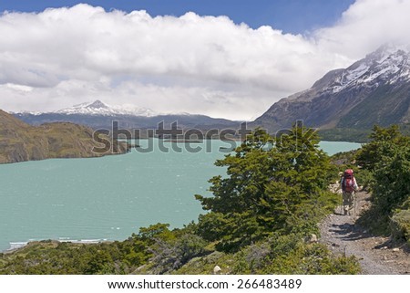 Backpacker on the W- trek trail along Lake Nordernskjold in Torres del Paine National Park in Patagonian Chile - stock photo