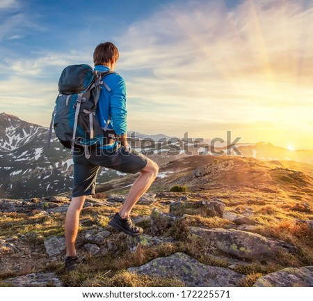 Backpacker on top of a mountaine - stock photo
