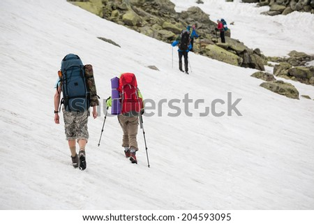 Backpacker passes snow field in rocky mountain in Altai mountains, Russia - stock photo