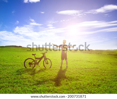 backpacker standing next to bicycle with sunrise background - stock photo