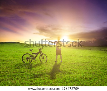 backpacker standing next to bicycle with sunset background - stock photo