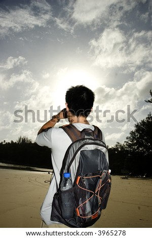 backpacker staring into sun on beach - stock photo