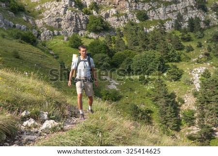 Backpacker walks at the mountains in the summer
