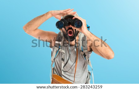 Backpacker with binoculars over colorful background - stock photo