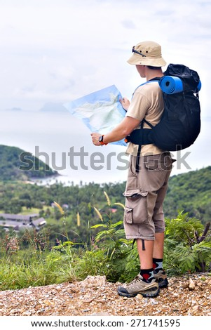 Backpacker with black rucksack reading map on the edge of a hill with view on green small island on the background - stock photo