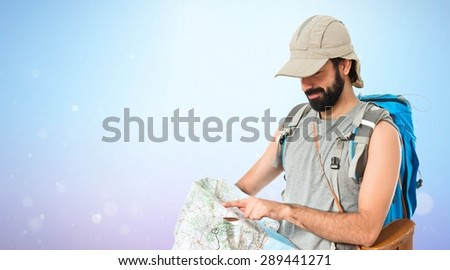 Backpacker with map over shiny background - stock photo
